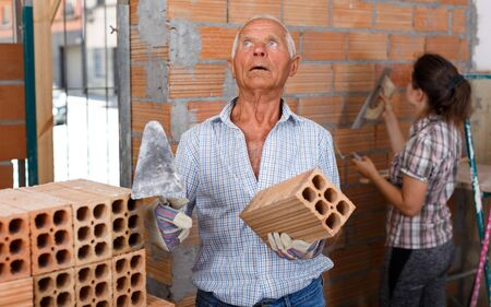 Focused elderly man working with daughter on their home renovations, installing brick wall inside