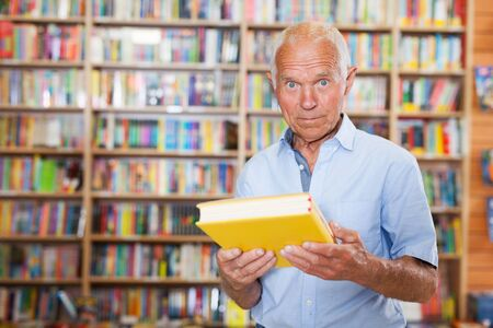 happy  mature man reading new books in bookshop