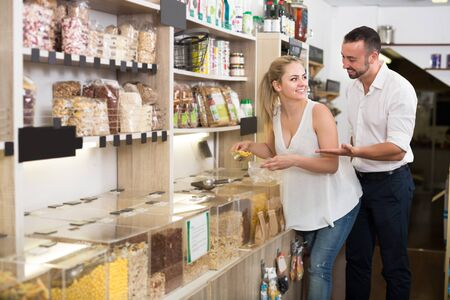 Young family taking with scoop cereals sold by weight in organic shop
