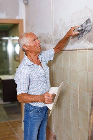 Hombre senior en camisa a cuadros y jeans masilla y renovación de paredes en su apartamento