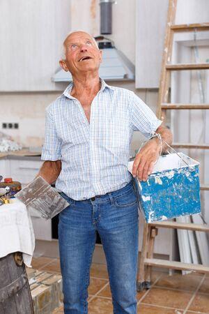 Hombre senior trabajando en la revisión de su casa, determinando el alcance de los trabajos de enlucido en interiores