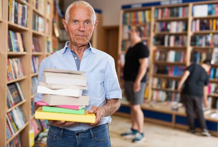 Portrait of elderly male buyer with pile of books in bookshop interior