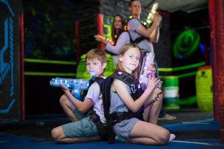 Two little confident laser tag players sitting back to back with guns on dark gaming arena Stok Fotoğraf