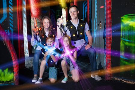 Group of happy kids and adults posing together in colorful beams of laser guns while having fun on dark lasertag arena Standard-Bild