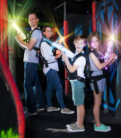 Cheerful little boy and girl standing back to back on bright beams with laser pistols in dark lasertag room during game with parents