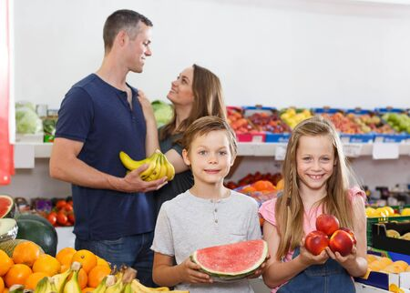 Cheerful preteen kids holding fresh delicious watermelon and  nectarines during family shopping Foto de archivo