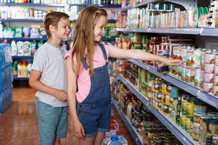 Smiling kids choose preserved meal for home in the supermarket