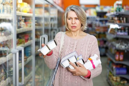 Portrait of positive aged woman choosing fresh dairy products on shelves in grocery store