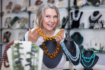 Adult woman chooses jewelry from turquoise and amber jewelery in the store 免版税图像