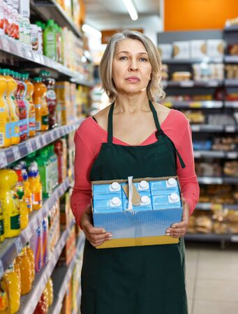 Experienced female grocery worker with packing of drinks working in shop, putting fresh products on shelves