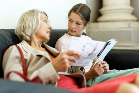 Mature woman and teenage girl sitting with paper guide during museum visit Foto de archivo