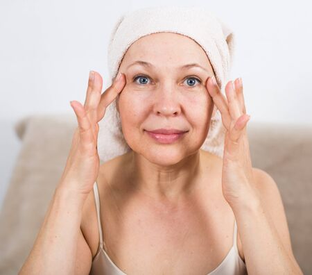 Mature woman applying face cream during beauty procedures at home