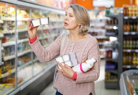 Shocked female reading product label while choosing groceries in supermarket