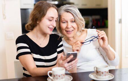 Rijpe moeder met volwassen dochter zitten met smartphone in keuken interieur