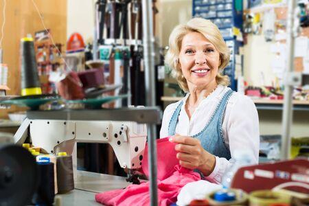 Charmante reife Frau Schneider mit Nähmaschine in der Werkstatt Standard-Bild