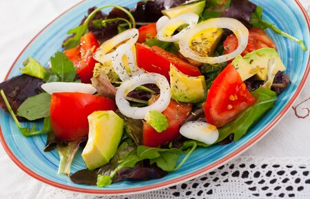 Image of salad with arugula, tomato and avocado on the plate indoors.