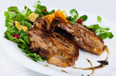 Primo piano di deliziose costolette di maiale fritte con avocado e frutti di bosco al piatto