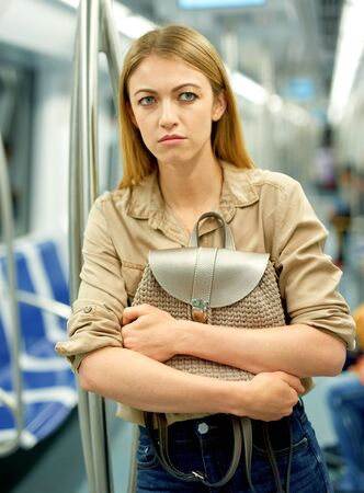 Blonde fears for her handbag in the subway car