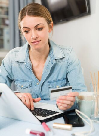 Girl buying online with laptop and credit card at home