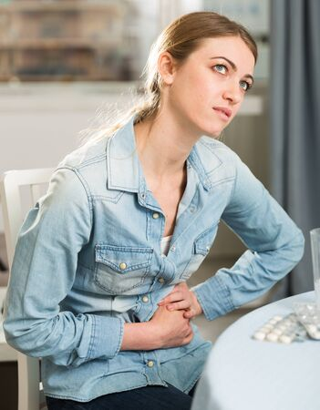 Young woman experiencing pain in the stomach