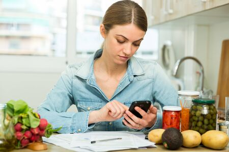 Serious young woman working with papers and using phone at home kitchen Imagens