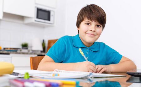 Ten years old boy studying at kitchen table, doing homework