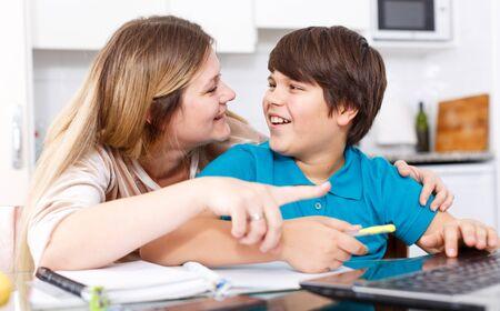 Vrouw helpt tweenage jongen met lessen die samen in de thuiskeuken zitten Stockfoto
