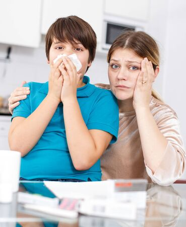 Worried woman sitting on kitchen with son blowing nose into napkin having flu or allergy