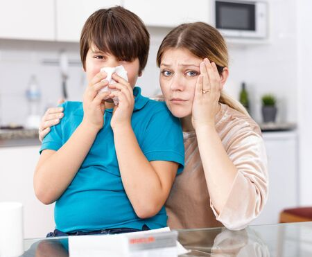 Tween boy with running nose and tissue sitting with worried mother at kitchen
