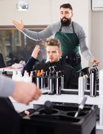 outraged man client expressing dissatisfaction about his haircut at hair salon stylist Foto de archivo