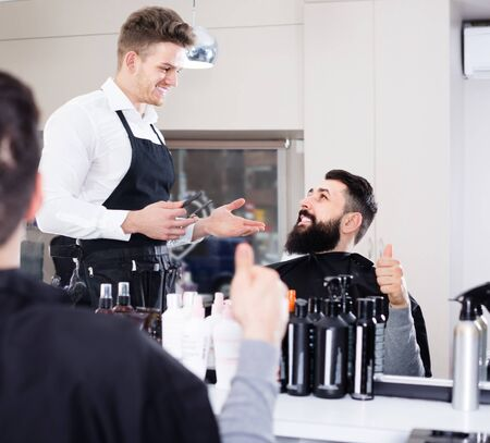 friendly guy stylist demonstrating final fashionable haircut to client at hairdressing salon