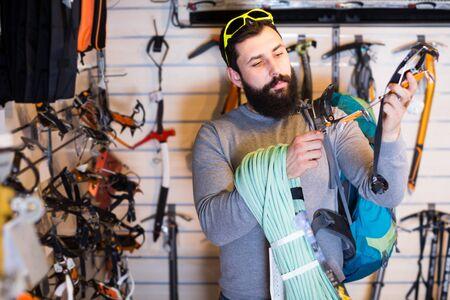 happy male customer examining assortment of climbing equipment in sports equipment store Reklamní fotografie