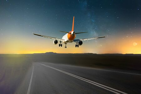 Airplane flying over roadway on background mountains and cloudscape