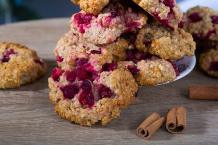 Closeup of homemade oatmeal cookies with berry on plate on wooden background