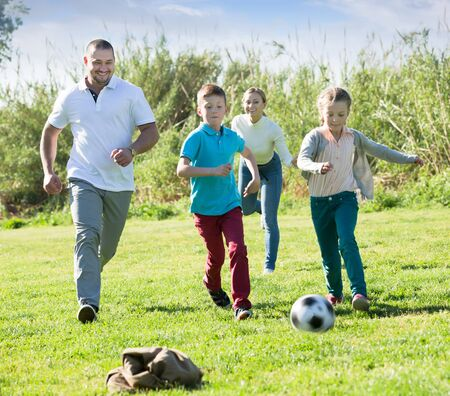 Happy parents with two kids playing soccer on the green field. Focus on man