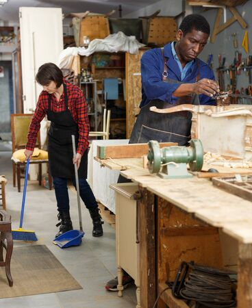 Portrait of male and female artisans in process of renewing vintage chest of drawers in workshop