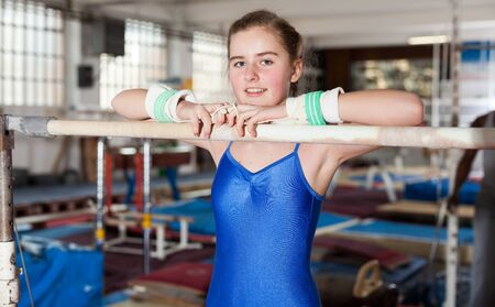 Positive teenage girl in gymnastic swimsuit training gymnastics at acrobatic hall