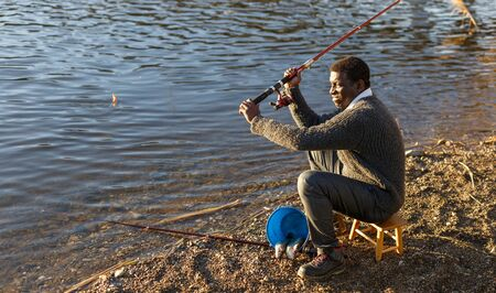 Positive African man sitting near river and holding fishing rod