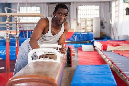 Portrait of adult african man training on gymnastic equipment in gym Foto de archivo - 125820024
