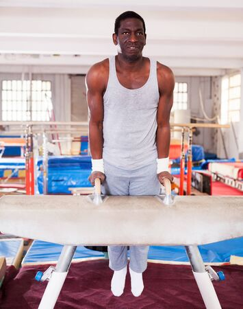 active young afro man in sportswear doing exercises on pommel horse in acrobatic hall Foto de archivo - 125820165