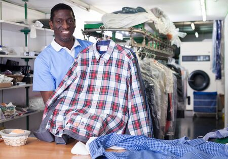 Cheerful African American man worker of dry cleaner standing at reception counter, showing clean clothes after dry cleaning Stock Photo