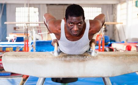 Portrait of happy cheerful  man in sportswear doing exercises on pommel horse at gymnastic hall Foto de archivo - 125820199