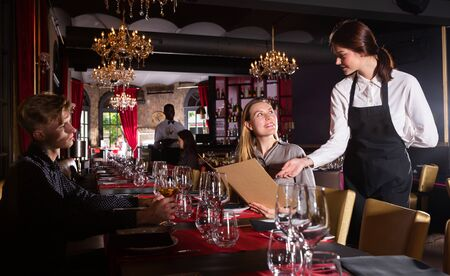 Young female waiter taking order from visitors in luxurious restaurant