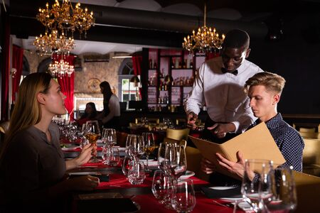 Polite african-american waiter bringing ordered dishes to couple at luxurious restaurant Imagens