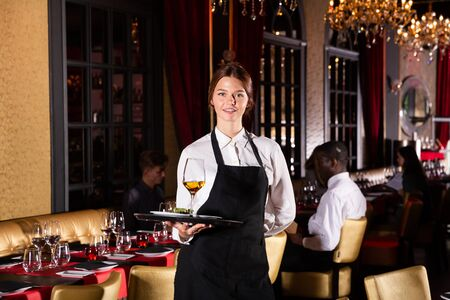Portrait of female waiter who is holding tray with order