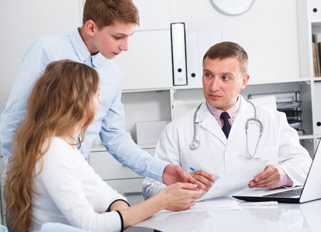 Visitante y su hijo adolescente consultor sonriente hombre médico en el hospital