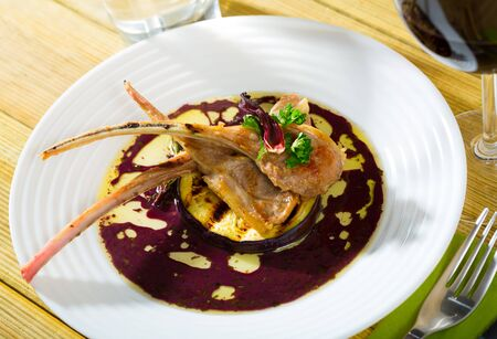 Delicious baked lamb ribs served on white plate with grilled eggplant, wine sauce, rosemary and dried hibiscus Standard-Bild
