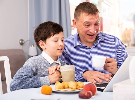 Portrait of young father and son with tea using laptop at table  indoors