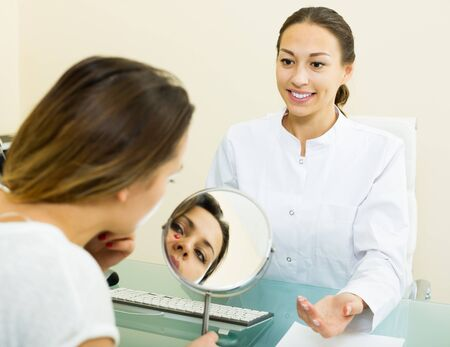 Smiling doctor and  female client in aesthetic medicine center