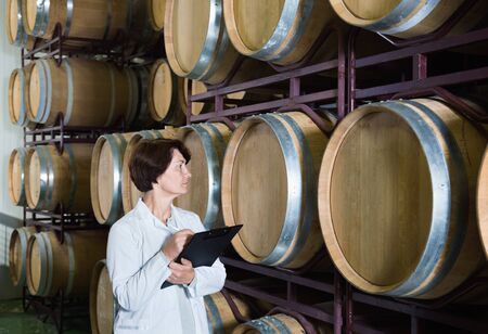 Diligent  friendly expert examines equipment at winery and writes down remarks